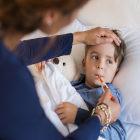 Criança com febre com termômetro na boca