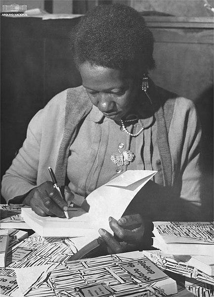 Carolina Maria de Jesus autografando seu livro Quarto de despejo, em 1960. [1]