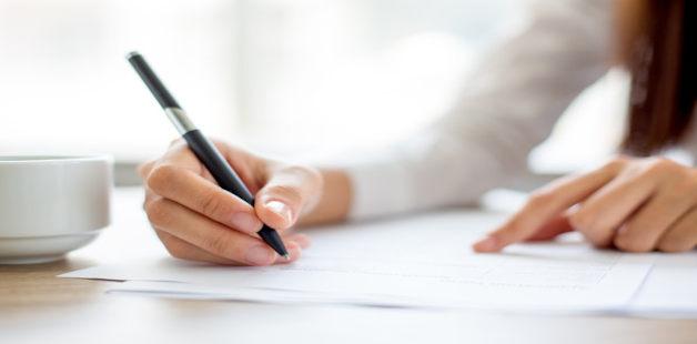 Mão de estudante escrevendo com caneta preta