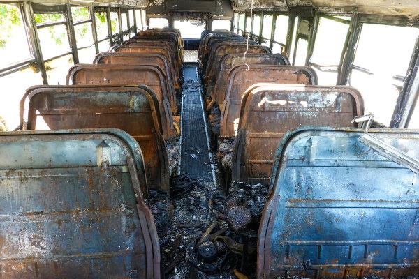Interior de um ônibus abandonado com bancos queimados.