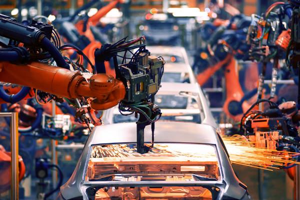 Foto de uma fábrica de carros com uma máquina funcionando.