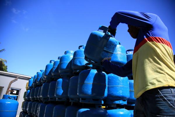 Funcionário de uma distribuidora de gás realizando entrega de um botijão, contendo o GLP. [1]