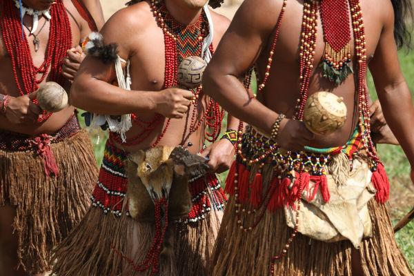 Indígenas em trajes típicos.