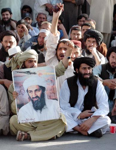 Homens muçulmanos reunidos e sentados; um deles segura o retrato de Osama bin Laden.