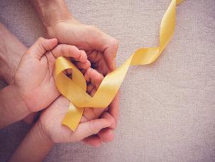 Mãos seguram laço amarelo