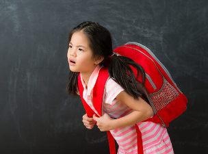 Criança com mochila nas costas e expressão de incômodo