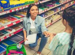 Professor e aluno em supermercado com caderno na mão