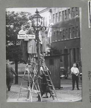 Berlinenses ocidentais acenando para seus amigos e familiares do outro lado do Muro de Berlim na Bernauer Straße.**