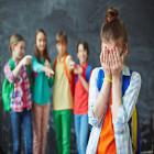 Menina vítima de bullying coloca as mãos no rosto