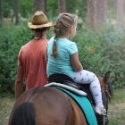 Criança montada em cavalo guiado por um homem