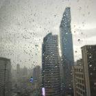 Gotas de água em vidro com prédios desfocados ao fundo