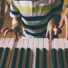 Criança aprendendo a tocar piano