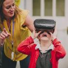 Professora ao lado de criança usando óculos de realidade virtual