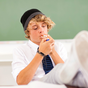 garoto branco fumando na sala de aula
