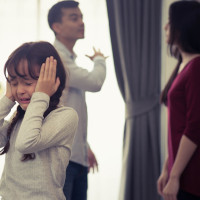 pais discutindo e criança com mãos no ouvido