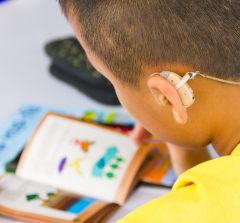Criança lendo livro com aparelho auditivo