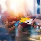 Mãos juntando peças de quebra-cabeça colorido